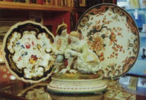 A continental porcelain group made in Paris for The Great Exhibition of 1851, flanked by a plate decorated around 1825 by Henry and Richard Daniel, and a Derby Stilton base of around 1790